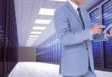 Businessman using digital tablet against server room background